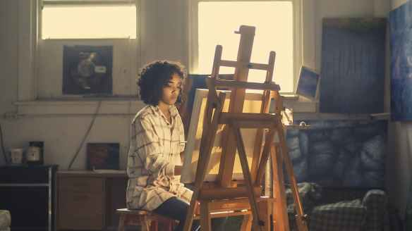 photo of woman painting in brown wooden easel